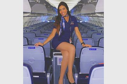 Стюардесса вмини-юбке попозировала натележке для еды наборту самолета